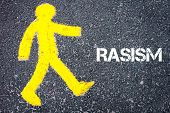 stock photo of pedestrians  - Yellow pedestrian figure on the road walking towards RASISM - JPG