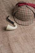 image of private investigator  - Deerstalker or Sherlock Hat and Tobacco pipe on Old Wooden table - JPG