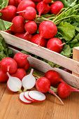 stock photo of crate  - Macro of fresh sliced red radish in wooden crate - JPG