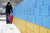 picture of children walking  - Father walking with a small child on a background of patriotic symbol of Ukraine