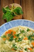 stock photo of nettle  - Nettle soup with eggs in blue plate with fresh nettle and spoon vertical - JPG