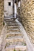 picture of gutter  - A narrow alley in Gordes in Provence France has just enough space for steps and two small gutters as it winds between buildings - JPG