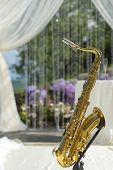 stock photo of saxophones  - Gold saxophone in festive wedding ceremony decor of lightweight white fabric on purple and violet natural background vertical picture - JPG