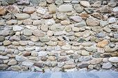 pic of fortified wall  - Old wall of stones and a pavement - JPG