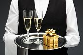 stock photo of flute  - butler with gift and two champagne flutes on tray - JPG