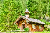 picture of chapels  - Mountain wooden chapel on a background of green pines - JPG