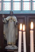 foto of sacred heart jesus  - Statue of Jesus Christ in Church with Lit Burning Candles in Foreground - JPG