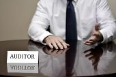 picture of irs  - IRS tax auditor business card at desk with hands gesturing - JPG