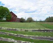 image of red barn  - rural farm fields with red barn viewed through old split rail fence - JPG