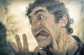 picture of crazy face  - Crazy lunatic man smooshes face against glass surfaces - JPG