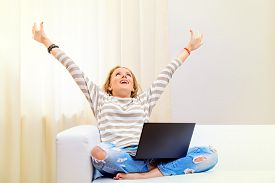 stock photo of social housing  - Young woman sitting on a sofa with her laptop computer raised her hands in the air - JPG