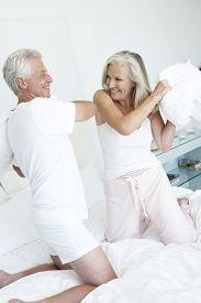 stock photo of pillow-fight  - Senior Couple in bedroom having pillow fight - JPG