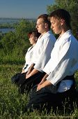 pic of aikido  - Three young aikido man meditate before training - JPG