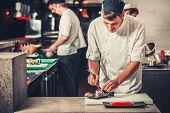male cooks preparing sushi in the restaurant kitchen poster