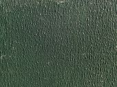 stock photo of stippling  - Sunlight highlights green stippled paint on board - JPG