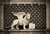 Lion of Venice statue in historical buildings at Piazza San Marco, Italy. poster