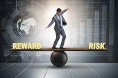 Businessman balancing between reward and risk business concept poster