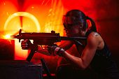 Young strong woman warrior shooting from machine gun in dramatic urban night scene. Tattoo on body. poster