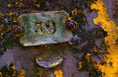 Rusty surface of an old industrial machine with a plate with the number 59