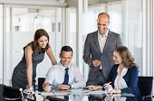 Happy business team in a meeting discussing about strategies in a modern board room. Businesspeople  poster