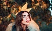 Gorgeous Pretty Woman In Furry Coat Fallen Leaf On Head As Crown. Trendy Outfit. Her Confidence Is S poster