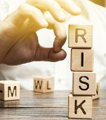 Hand Removes Blocks With The Word Risk. The Concept Of Reducing Possible Risks. Insurance, Stability poster