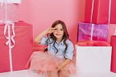 Pretty Joyful Young Girl In Tulle Skirt Sitting Suround Colorful Giftboxes On Pink Background. Lovel poster