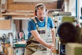 Absorbed carpenter with ear protection and safety goggles at the milling machine working on wood poster