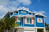 Large Beach House Painted In Dark Blue With White Trim And Coral Shutters. House Has Roof Deck, Gara poster