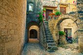 Picturesque Narrow Street With Stone Houses. Rustic Stone Houses And Entrances Decorated With Flower poster