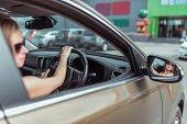 A Girl Driving A Right-hand Drive Car Is Parked In A Parking Lot, Near A Shopping Center, Left-hand  poster