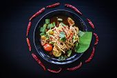 Papaya Salad Served On Black Background / Green Papaya Salad Spicy Thai Food On Plate With Herbs And poster