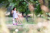 Happy girl rides on a rope swing with her retro doll in park. Little Princess has fun outdoor, summe poster