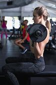 Side view of Caucasian Fit woman exercising with barbell in fitness center. Bright modern gym with f poster