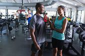 Front view of African-american Fit man and woman interacting with each other in fitness center. Brig poster