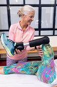 Front view of Happy Caucasian active senior woman assisting disabled Caucasian woman to stretching l poster
