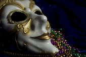 image of mardi-gras  - White and gold Mardi Gras mask and beads on a blue velvet background - JPG