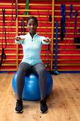Front view of woman exercising with exercise ball in sports center. Sports Rehab Centre with physiot poster