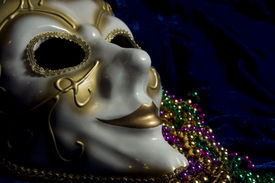 image of mardi gras mask  - White and gold Mardi Gras mask and beads on a blue velvet background - JPG