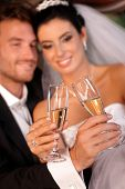 Bride and groom clinking glasses on wedding-day. Focus on champagne flutes.