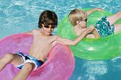 Male friends relaxing on inflatable ring while holding hands in pool