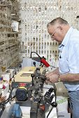 picture of locksmith  - Side view of senior locksmith making key in store - JPG