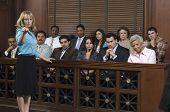 Portrait of a female advocate pointing with jurors sitting together in the witness stand at court ho