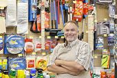 Portrait of a happy middle-aged salesperson with arms crossed in hardware store