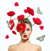 Beauty Fashion Model Woman with Red Poppy Flowers in her Hair. Perfect Creative Make up and Hair Sty