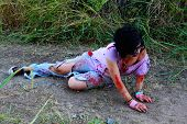 stock photo of gruesome  - A woman in bloody clothes pretends to be a zombie - JPG