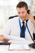 businessman talking on landline phone looking at business documents handheld