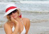 foto of coy  - Pretty blond on a beach in sunglasses and sun hat giving a coy look - JPG