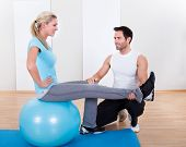 Instructor Helping A Woman With Pilates Exercises