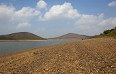 stock photo of karnataka  - south indian landscape with clouds in blue sky over rolling hills of karnataka viewed across the rocky shores of kabini river - JPG
